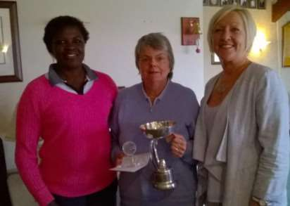 Helen Pollard collects her Par Trophy from sponsor Mo Arnold and Lady Captain Ngoneh Dickinson.
